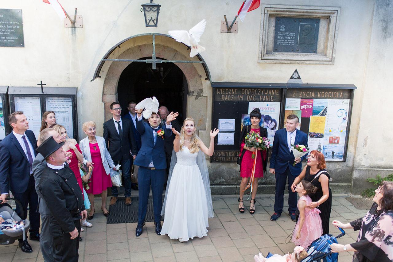 Gołębie ślubne. Białe gołębie wypuszczone przez Pare Młoda na ślubie w Krakowie. Fotograf ślubny z Krakowa.